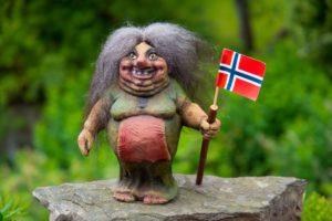 Kvinnelig trollfigur med stav og norsk flagg i hånden